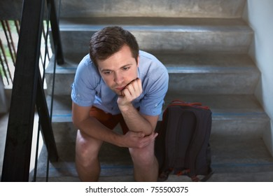 A young man is sitting on the stairs and sad. He lost the keys to the apartment, or he was kicked out of the house during a quarrel.