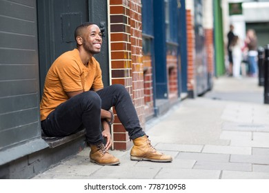 young man sitting on a step in the street