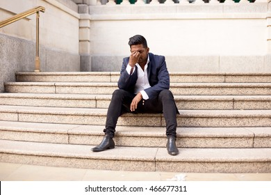 young man sitting on steps in the street with a headache