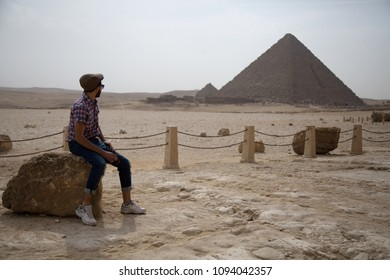 Young man sitting on a stone on the front of the pyramid looking at the pyramid behind him.