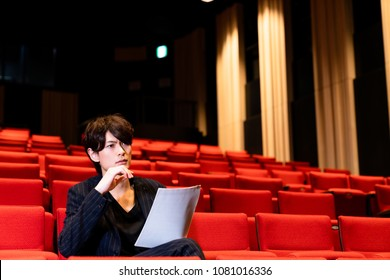 young man sitting on theater seat.