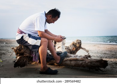 the young man sitting on the timber at the beach and play internet on the smart phone