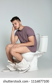 Young man sitting on toilet bowl against gray background