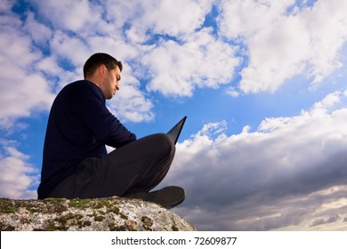 Young man sitting on the top of mountain working with laptop