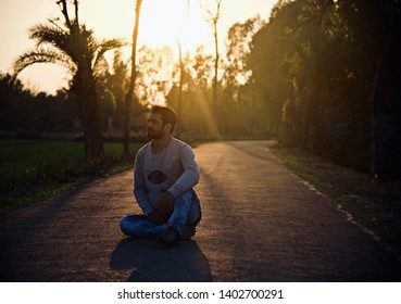 Young man sitting on an urban street in the afternoon