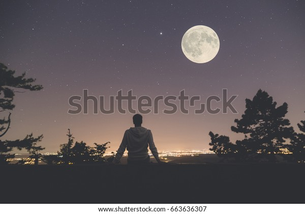 Young man sitting on the wall at night. City lights, moon and stars in the background.