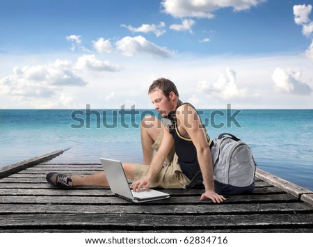 Young man sitting on a wharf and using a laptop