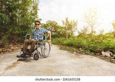 Young man sitting on wheelchair, teenager disabled person concept outdoor nature background.