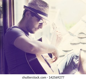 Young man sitting on the window playing the guitar. Stylish hipster guy with hat and sunglasses enjoys music and summer holiday. Retro filter.