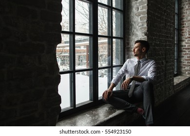 Young man is sitting on windowsill and looking out on a bright day