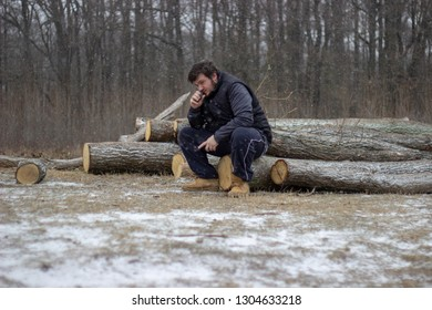 young man is sitting on wood on snowy ground with forest in the background wearing dark clothes inhaling the ecigarette