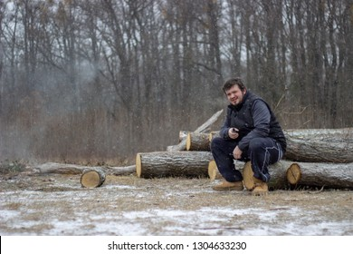 young man is sitting on wood with forest in the background wearing dark clothes holding  the ecigarette and looking straight to the camera