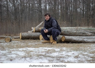 young man is sitting on wood on snowy ground with forest in the background wearing dark clothes holding the ecigarette
