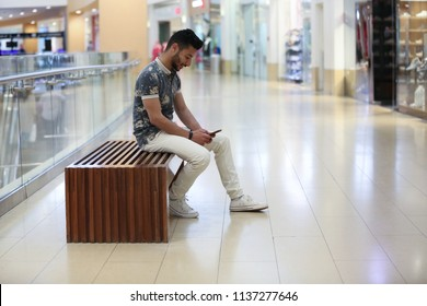 Young man sitting on a wooden bench in a mall porch holding his phone surfing in a side shot.