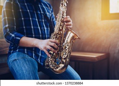 A young man sitting on wooden chair and plays saxophone in modern studio with window light, music background with copy space.