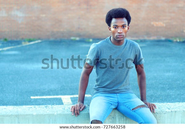 young man sitting outdoor in parking jeans and t-shirt
