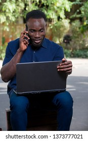 young man sitting outdoors going to communicate with mobile phone and looking at laptop smiling.