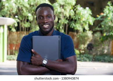 young man sitting outdoors with laptop computer looking at camera smiling.