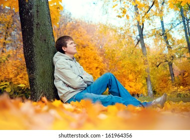 a young man sitting outdoors in a park in autumn
