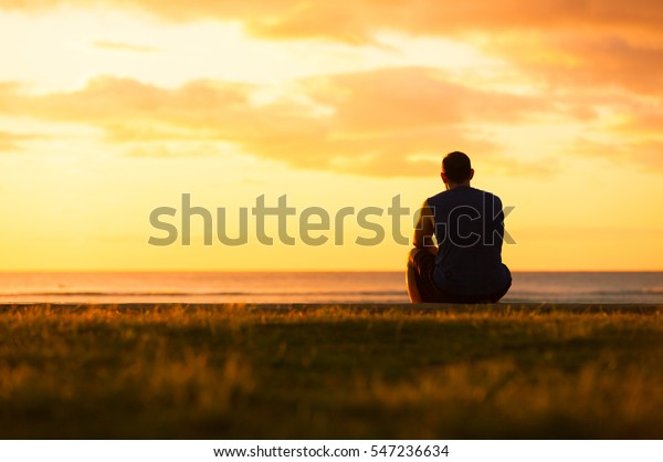 Young man sitting outdoors watching the sunset. Thinking and relaxing concept.