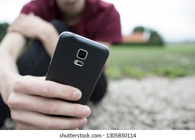 A young man sitting outside in the garden, holding a black smartphone in his hand. His fingers are close to the camera. A concept about being totally addicted to your phone or trying to reach somebody