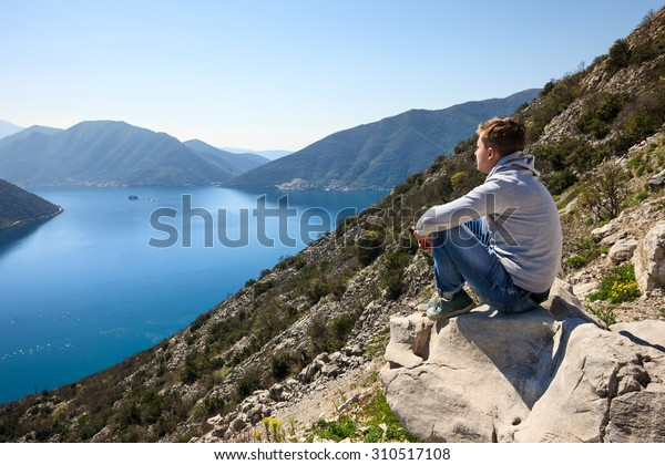 A young man sitting over the sea at the rock and contemplating beautiful Kotor bay in Montenegro