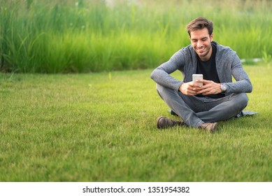 Young man sitting in the park, enjoying a nice conversation over his cell phone, surrounded by green grass; casual scene