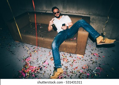 Young man sitting at a party, having a great time.
