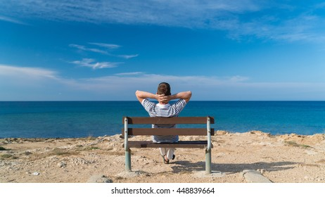 Young man sitting relaxed on a bench at a sea with his hands behind head and enjoying the view