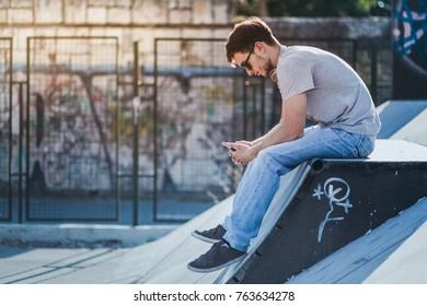 Young man sitting at skate park at sunset