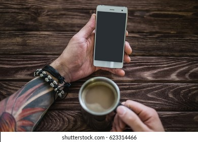 Young man sitting with a smartphone and a cup of coffee at a wooden table, point of view. Free space on screen of phone.