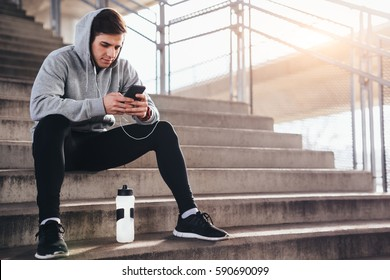 Young man sitting at the stairs and using mobile phone