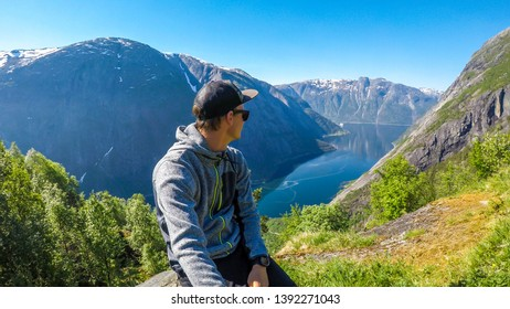A young man sitting at the stone and looking back at the view of Eidfjord from Kjeasen, Norway. Slopes of the mountains are overgrown with green grass. Water is dark blue. Man is taking a selfie
