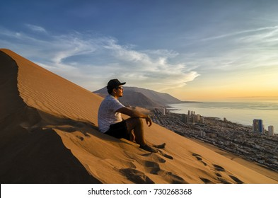 Young man sitting at the summit of enormours sand dune and overlooking city and ocean at the sunset