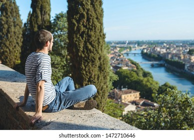 young man sitting in sun and looking at city and river view