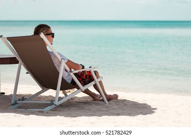 Young man sitting in sunbed at the beach