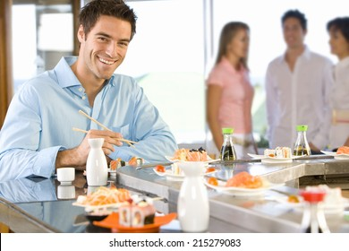 Young man sitting at sushi bar, smiling, portrait