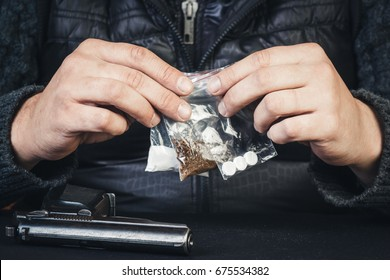 Young man sitting at the table with arms holding packages with drugs. Drug addiction, crime.