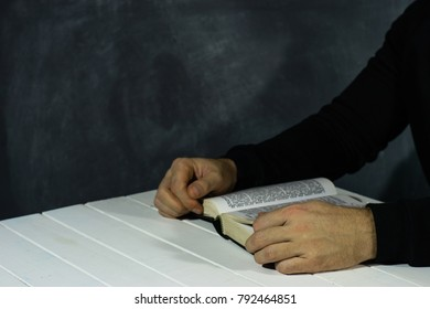 Young man sitting at a table reading the Holy Bible