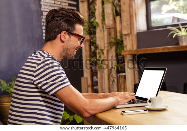 Young man sitting at table using laptop in cafeteria