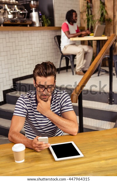 Young man sitting at table using a smartphone in cafeteria