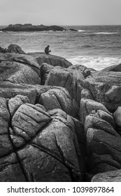 Young man is sitting and taking a picture on the rocks near by the North sea, Norway. White waves on background.