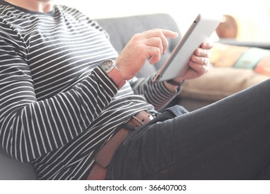 Young man sitting using a tablet, Dressed casually. Vintage post processed. Urban life style, technology, online, business, shopping, fashion and job hunting concept.