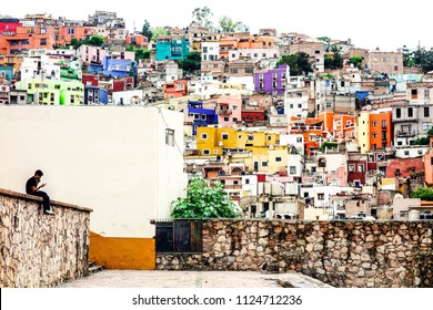 Young man sitting in a wall with Guanajuato colorful houses background. Guanajuato, June 2015, Mexico.