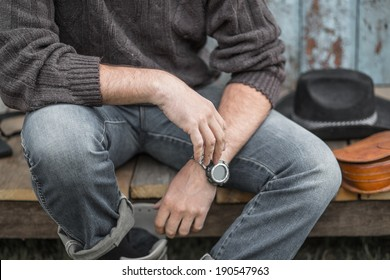 Young man sitting wearing jeans outdoor. focus on right hand