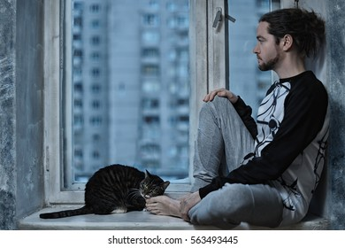 Young man sitting at the window with her cat