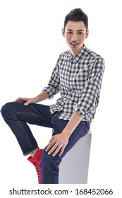 young man sitting wooden cube posing in studio