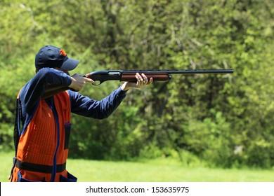 Young man skeet shooting