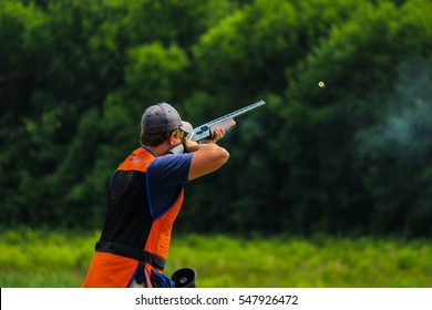 Young man skeet shooting outdoors; shooting clay pigeon targets at gun club with airborne casing and copy space