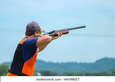 Young man skeet shooting outdoors; shooting clay pigeon targets at gun club with casing exiting gun and copy space